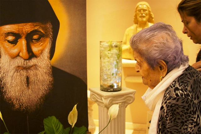 July 26, 2013MiamiJONATHAN MARTINEZ | FCLourece Gahnoum prays before an image of St. Charbel after being anointed with holy oils bought from the hermit's tomb in Lebanon.